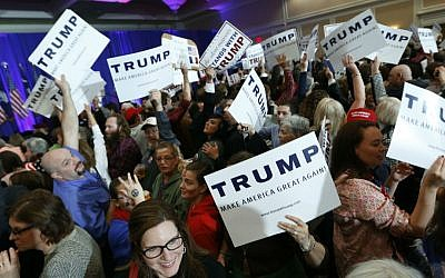 Supporters for Republican presidential candidate Donald Trump hold signs during a South Carolina Republican primary night event Saturday, Feb. 20, 2016, in Spartanburg, South Carolina. (AP Photo/Paul Sancya)