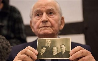 Auschwitz concentration camp survivor Leon Schwarzbaum presents an old photograph showing himself, left, next to his uncle and parents who all died in Auschwitz, during a press conference in Detmold, Germany, Wednesday, Feb. 10, 2016. (Bernd Thissen/dpa via AP)