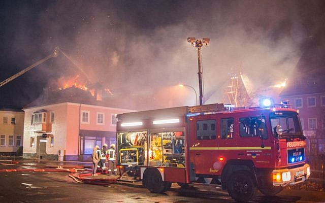 A fire engine stands in front of a burning building in Bautzen, eastern Germany, Sunday, February 21, 2016. (Rico Loeb/dpa via AP)