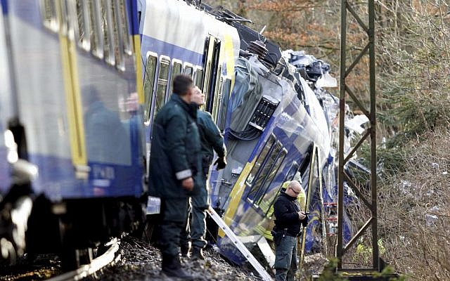 Police stand beside two trains that collided head-on near Bad Aibling, southern Germany, Tuesday, Feb. 9, 2016 (Uwe Lein/dpa via AP)