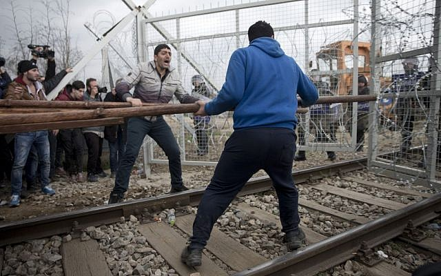 Refugees and migrants try to break an iron fence from the Greek side of the border as Macedonian police stand guard, near the northern Greek village of Idomeni on Monday, February 29, 2016. (AP/Petros Giannakouris)