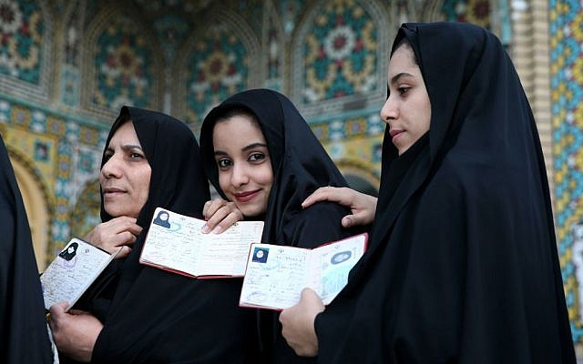 Iranian women show their identification, as they queue in a polling station to vote for the parliamentary and Experts Assembly elections in Qom, 125 kilometers (78 miles) south of the capital Tehran, Iran, Friday, Feb. 26, 2016. (AP Photo/Ebrahim Noroozi)