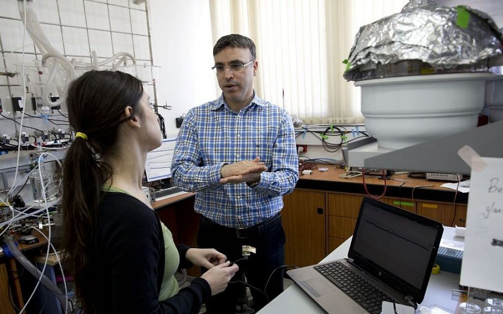 Professor Hossam Haick talks to a researcher in his lab at Technion University in Haifa, Israel, February 14, 2016. (AP Photo/Dusan Vranic)