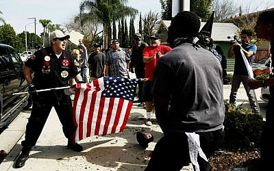 Illustrative: A Ku Klux Klansman, left, uses an American flag to fend off angry counter protesters after members of the KKK tried to start a 'White Lives Matter' rally at Pearson Park in Anaheim, California, on Saturday, Feb. 27, 2016. (Luis Sinco/Los Angeles Times via AP)