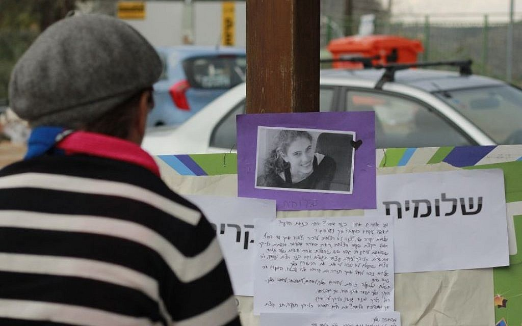 A Beit Horon resident reads the memorial set up for Shlomit Krigman on January 27, 2016. Krigman was killed in a terror attack in the West Bank settlement earlier in the week. (Judah Ari Gross/Times of Israel)