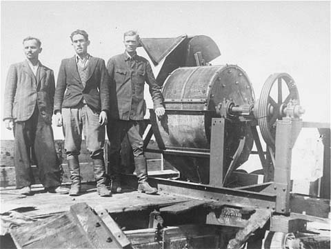 Jewish prisoners forced to work for a Sonderkommando 1005 unit pose next to a bone crushing machine in the Janowska concentration camp (ushmm.org via wikipedia)