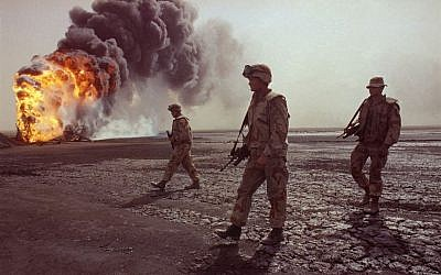 In this March 7, 1991 file photo, a U.S. Marine patrol walks across the charred oil landscape near a burning well during perimeter security patrol near Kuwait City.  (AP Photo/John Gaps III, File)