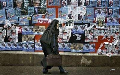 An Iranian woman walks past electoral posters of parliamentary election candidates on a sidewalk in downtown Tehran, Iran, Wednesday, Feb. 24, 2016. (AP Photo/Vahid Salemi)