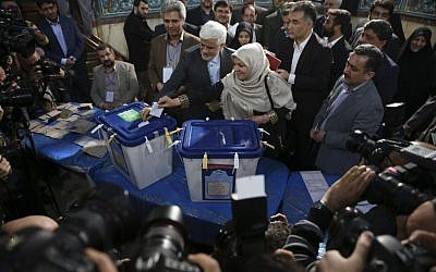 Head of the reformists' coalition list of the Iranian parliamentary elections in Tehran Mohammad Reza Aref, center, and his wife Hamideh Moravej Farshi cast their ballots at a polling station in northern Tehran, Iran, Friday, Feb. 26, 2016. (AP Photo/Vahid Salemi)
