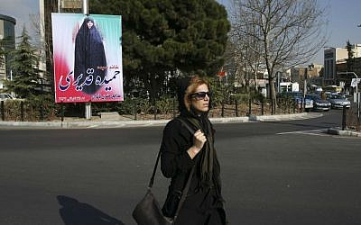 "An Iranian woman walks in front of an electoral banner of Hamideh Ghadiri, a candidate in parliamentary elections in Vanak square in northern Tehran, Iran, Thursday, Feb. 25, 2016. The banner reads in Persian: ""Hamideh Ghadiri - defender of women's rights."" (AP Photo/Vahid Salemi)"