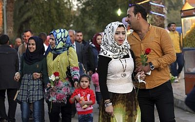 In this Saturday, Feb. 13, 2016 photo, Iraqis hold Valentine's Day gifts at Zawra Park in Baghdad, Iraq. Baghdad is plastered with Valentine hearts and roses, and Iraqis are enjoying a rare lull in violence but wondering how long it will last. (AP Photo/Hadi Mizban)