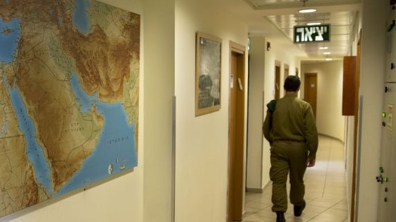 """An Israeli soldier walks in an office of the """"Roim Rachok"""" program in downtown Tel Aviv on Feb. 9, 2016. The program provides training and assistance to Israelis on the autism spectrum who wish to enlist in the military (AP Photo/Sebastian Scheiner)"""