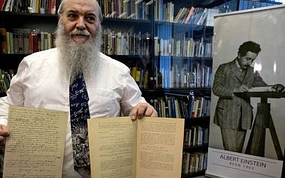 Hebrew University's Roni Gross holds the original historical documents related to Albert Einstein's prediction of the existence of gravitational waves at Hebrew University in Jerusalem, Thursday, Feb. 11, 2016. In a blockbuster announcement, scientists said Thursday that after decades of trying, they have detected gravitational waves, the ripples in the fabric of space-time that Einstein predicted a century ago. (AP Photo/Sebastian Scheiner)