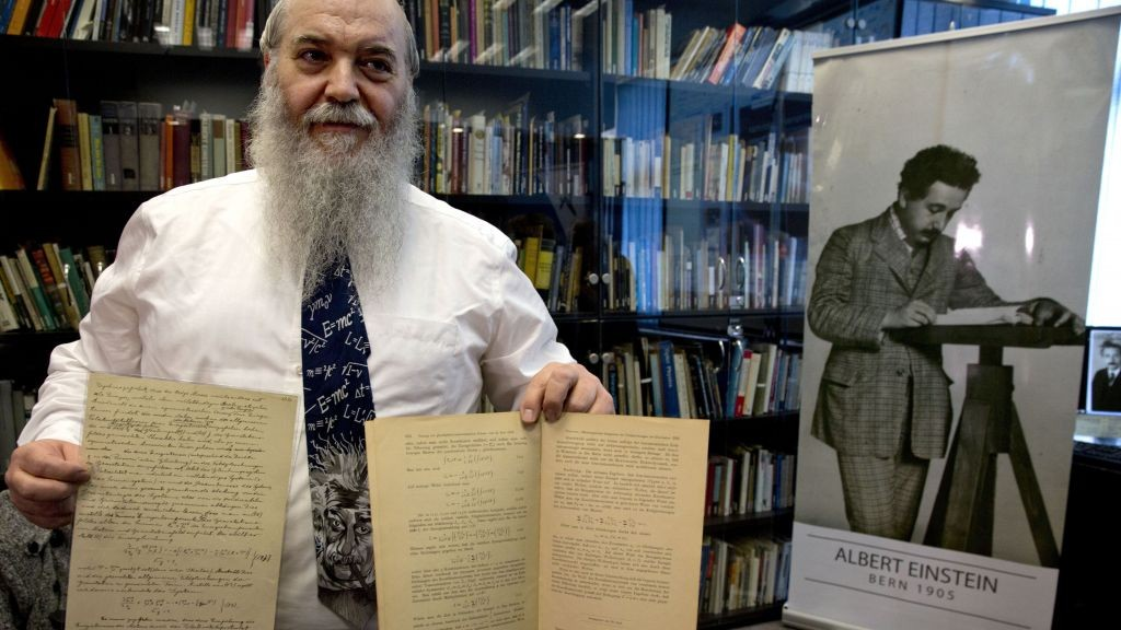 Hebrew University's Roni Gross holds the original historical documents related to Albert Einstein's prediction of the existence of gravitational waves at the Hebrew University in Jerusalem, Thursday, Feb. 11, 2016. In a blockbuster announcement, scientists said Thursday that after decades of trying, they have detected gravitational waves, the ripples in the fabric of space-time that Einstein predicted a century ago. (AP Photo/Sebastian Scheiner)