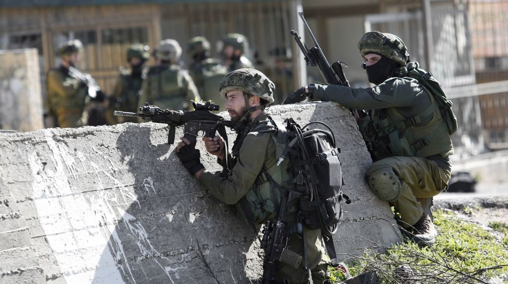 In this Monday, Feb. 15, 2016 file photo, Israeli soldiers take positions during a raid to arrest a Palestinian at the Amari Palestinian refugee camp, near the West Bank city of Ramallah. Nasser Shiyoukhi/AP)