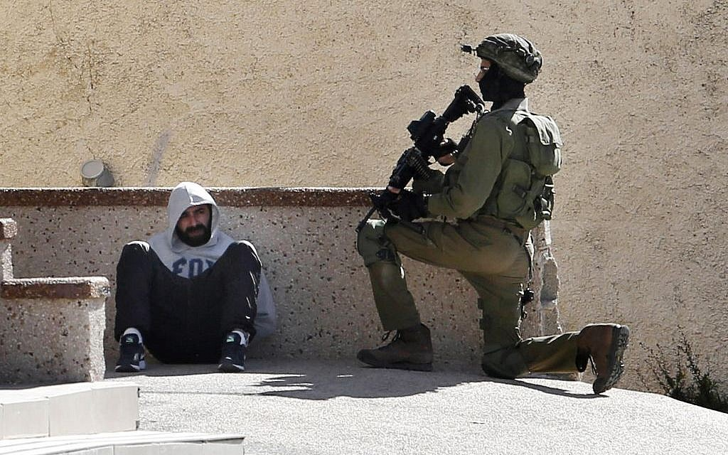 In this Feb. 15, 2016 file photo, an Israeli soldier keeps guard by an arrested Palestinian man at the Amari refugee camp, near the West Bank city of Ramallah. (AP Photo/ Nasser Shiyoukhi, File)