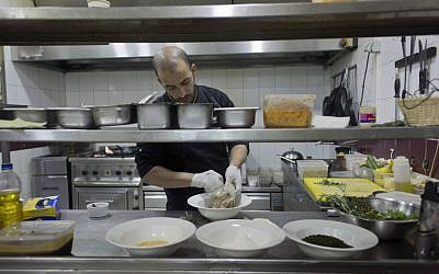 In this photo taken on Saturday Feb. 20, 2016, Palestinian chef Jihad al-Maharmeh prepares a mixed Palestinian French dish, Freekeh lamb rack at Orjuwan restaurant in the West Bank city of Ramallah. At a time of simmering Mideast tensions and rising malaise, a group of French chefs recently visited the West Bank to bring a little joie de vivre to Palestinian kitchens. (AP Photo/Nasser Nasser)