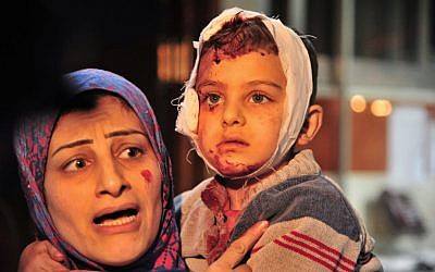 In this photo released by the Syrian official news agency SANA, a woman carries a child injured in the triple blast in Sayyida Zeinab, a predominantly Shiite Muslim suburb of the Syrian capital Damascus arrives to a hospital to receives treatment, Syria, Sunday, Feb. 21, 2016. (SANA via AP)