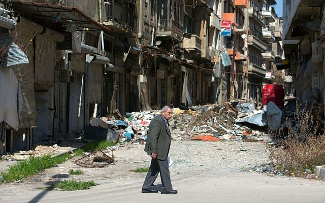 A Syrian man walks through a devastated part of the old city of Homs, Syria, February 26, 2016. (AP/Hassan Ammar)