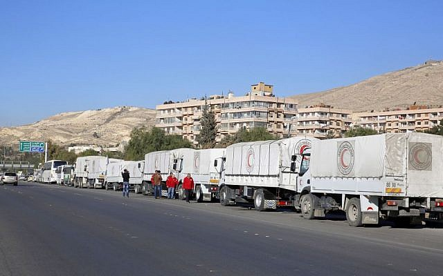 A convoy of humanitarian aid waits in front of the UNRWA offices before making their way into the rebel-held towns of Madaya, Zabadani and al-Moadhamiya in the Damascus countryside, as part of a UN-sponsored aid operation, in Damascus, Syria, February 17, 2016. (AP)
