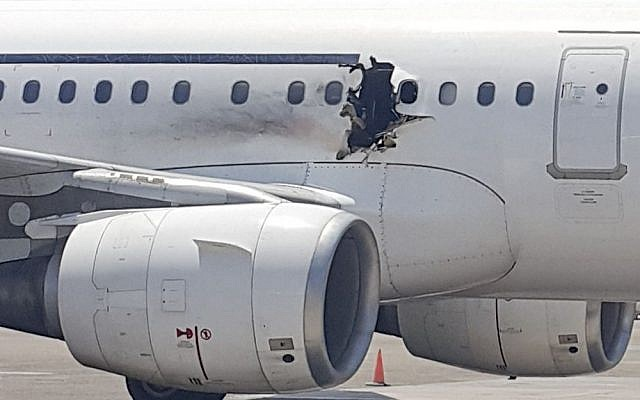 In this Tuesday, Feb. 2, 2016 photo, a hole is photographed in a plane operated by Daallo Airlines as it sits on the runway of the airport in Mogadishu, Somalia. (AP Photo)