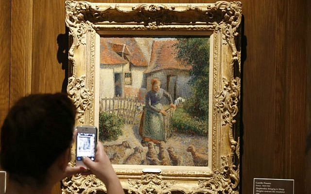 """In this Feb. 8, 2014, file photo, a visitor to the Fred Jones Jr. Museum of Art at the University of Oklahoma in Norman, Oklahoma, takes a photograph of a piece called """"Shepherdess Bringing in Sheep"""" by French impressionist artist Camille Pissarro, at the museum. (AP Photo/Sue Ogrocki, File)"""