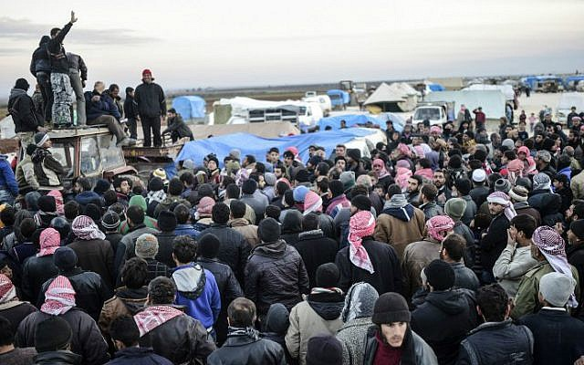 Syrians fleeing the embattled northern city of Aleppo wait near a crossing into Turkey in Bab-Al Salama, near the northern city of Azaz, on February 5, 2016. (AFP/Bulent Kilic)