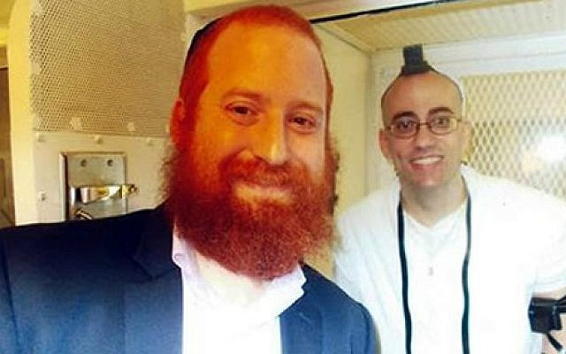 Rabbi Dovid Goldstein, director of Chabad-Lubavitch of West Houston and a chaplain in the Texas prison system, with death-row inmate Jedidiah Murphy, who donned tefillin for the first time to celebrate his bar mitzvah. (Courtesy Chabad.org)
