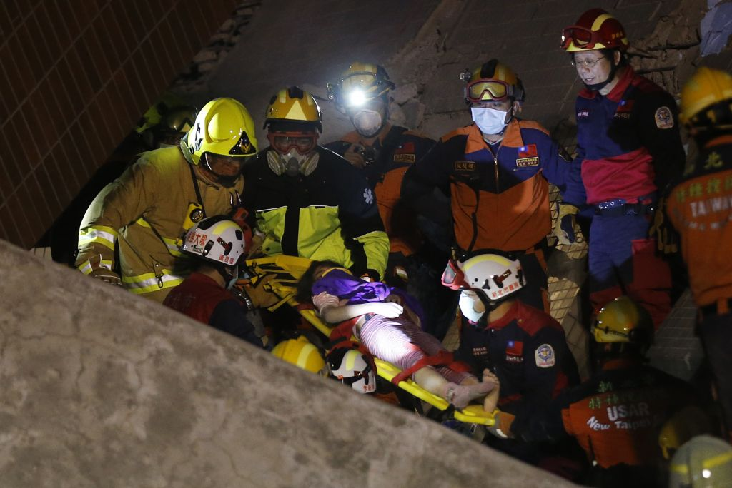 A female is rescued from a collapsed building complex after an early morning earthquake in Tainan, Taiwan, Saturday, Feb. 6, 2016. (Wally Santana/AP)