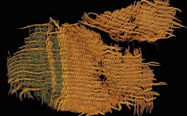 Fine wool textile dyed red and blue. The textile used the varying colors of natural animal hair to create black and orange-brown colors for decorative bands. (Clara Amit/Israel Antiquities Authority)
