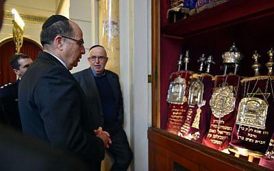 Defense Minister Moshe Ya'alon looking at Torah scrolls in Bern, Switzerland, on February 10, 2016. (Ariel Hermoni/Defense Ministry)