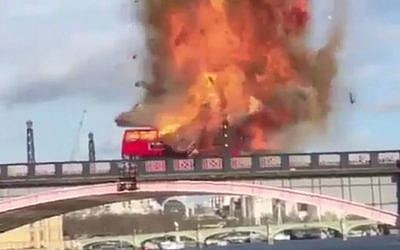 "An iconic London double decker bus exploding on a bridge during the filming of the Jackie Chan and Pierce Brosnan action movie ""The Foreigner."" (Screen capture/Twitter)"
