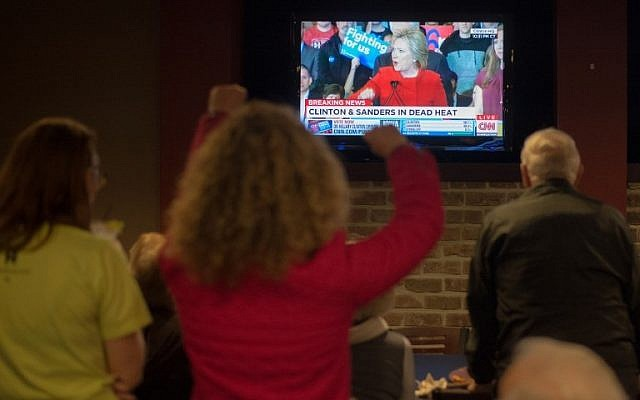 Staff and volunteers of the Hillary Clinton Burlington, Iowa campaign field office cheer as Hillary Clinton speaks on the television at the Boogaloo Cafe on February 1, 2016 in Burlington, Iowa. (AFP / Michael B. Thomas)