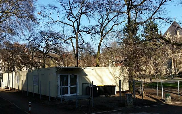 Teenage refugees live in these containers, located in a public park in Cologne, Germany. In the background, the city's Roonstrasse synagogue (Raphael Ahren/TOI)