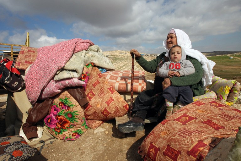 A Palestinian woman sits holding a child next to items salvaged from the remains of their home after it was demolished by Israeli bulldozers in a disputed military zone in the area of Musafir Jenbah, which includes several villages, south of the West Bank town of Hebron on February 2, 2016. / AFP / HAZEM BADER