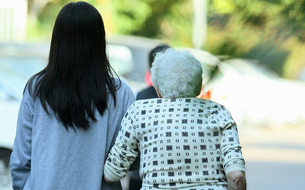An illustrative photo of a Filipina worker helping an elderly woman on November 2, 2010. (Moshe Shai/Flash90)
