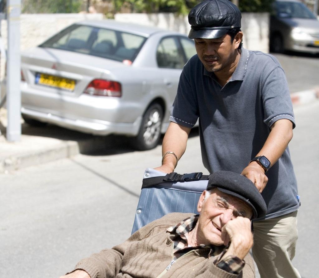 A Filipino man works taking care of an elderly Israeli man sitting in a wheel chair. (Illustrative photo by Abir Sultan/Flash90)