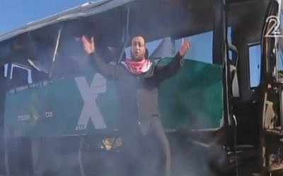 A still image from a Hamas video in praise of suicide bombings released on February 7, 2016 shows a group member standing in front of a burnt out Israeli bus (screen capture: YouTube)