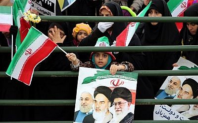 An Iranian girl holds a poster showing President Hassan Rouhani (left), previous leader Ayatollah Ruhollah Khomeini (center) and Supreme Leader Ayatollah Ali Khamenei (right) during celebrations in Tehran to mark the 37th anniversary of the Islamic Revolution, on February 11, 2016. (AFP/Atta Kenare)