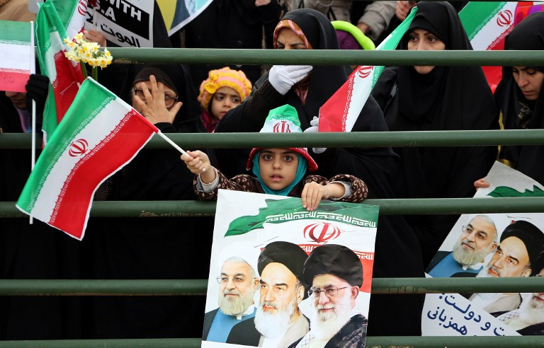 An Iranian girl holds a poster with a portrait of President Hassan Rouhani (L), Iran's late leader Ayatollah Ruhollah Khomeini and Iran's Supreme Leader Ayatollah Ali Khamenei during celebrations in Tehran's Azadi Square (Freedom Square) to mark the 37th anniversary of the Islamic revolution on February 11, 2016. (AFP / ATTA KENARE)