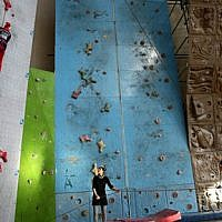 In this Monday, Jan. 18, 2016 photo, Iranian rock climber, Farnaz Esmaeilzadeh, top left, scales a wall in a rock climbing gym as her mother and her friend support her, in the city of Zanjan, some 330 kilometers (207 miles) west of the capital Tehran, Iran. (AP Photo/Ebrahim Noroozi)