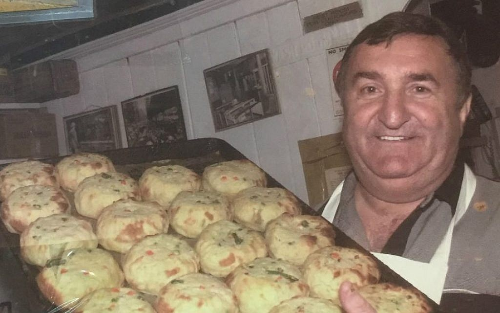 Alex Wolfson, seen here holding a tray of hot pastry, co-owns Yonah Schimmel's Knish Bakery with his daughter, Ellen Anistratov. The pair are descendants of the original owner, and the business is one of the few ongoing Jewish landmarks in New York's Lower East Side. (courtesy Ellen Anistratov)