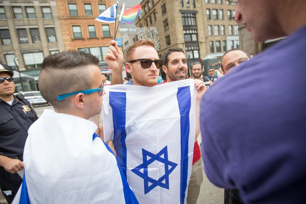 "Brett Loewenstern, center with Israeli flag, protested a Palestinian ""die-in"" event staged on the Boston Common on July 19, 2014. (Elan Kawesch/The Times of Israel)"