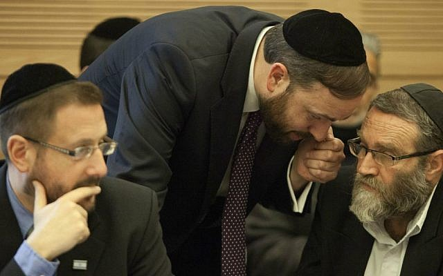 MKs Moshe Gafni, right, and Ariel Atias, center, discuss their strategy in opposing a bill requiring Haredim to join the army, not realizing that Lipman, a staunch advocate of the bill, can hear every word. February 17, 2014. (Flash90)