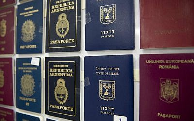 A presser, counterfeit passport printing plates and fake passports are displayed at the immigration bureau in Bangkok on February 10, 2016. (NICOLAS ASFOURI / AFP)