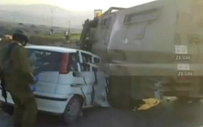 An IDF soldier inspects a vehicle that crashed into an Israeli APC when its driver was shot dead as he tried to ram into Israeli troops at the West Bank village of Silwad, on February 19, 2016 (screen capture: Channel 2)