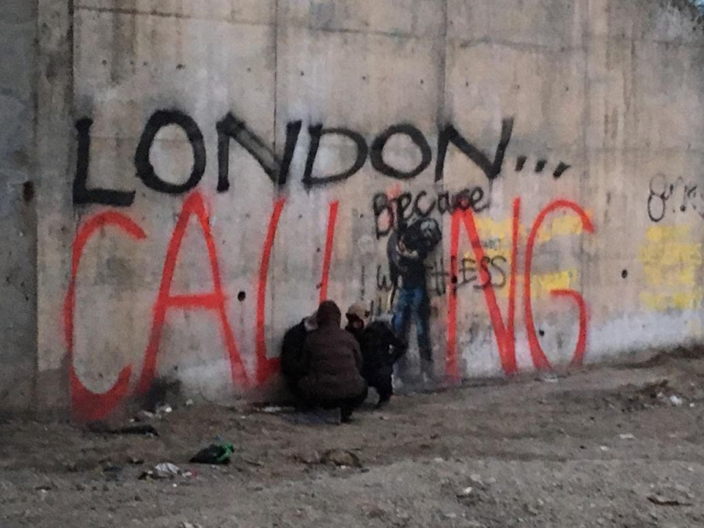 Street artist Bansky's 'London Calling' wall at the front of the Calais camp, with refugees sheltering beneath, February 8, 2015. (Alex Goldberg)