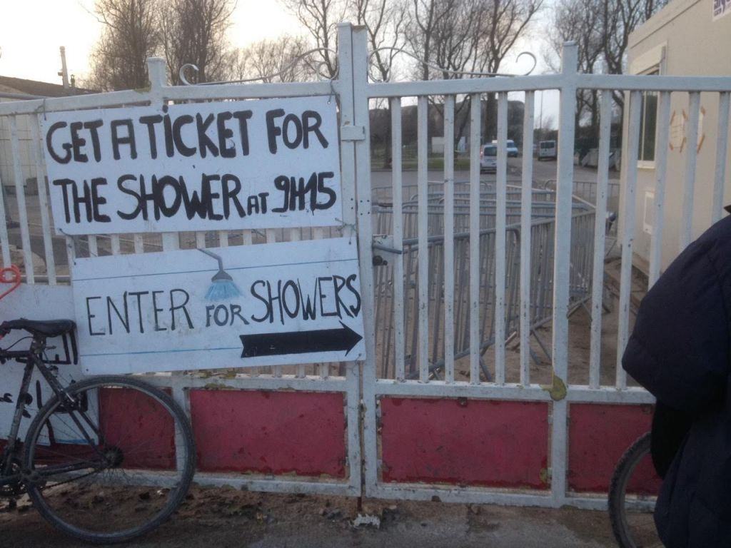 As sign pointing to shower facilities run by the French authorities at Calais camp in February 8, 2015. Each shower must be no longer than six minutes. (Jenni Frazer/The Times of Israel)
