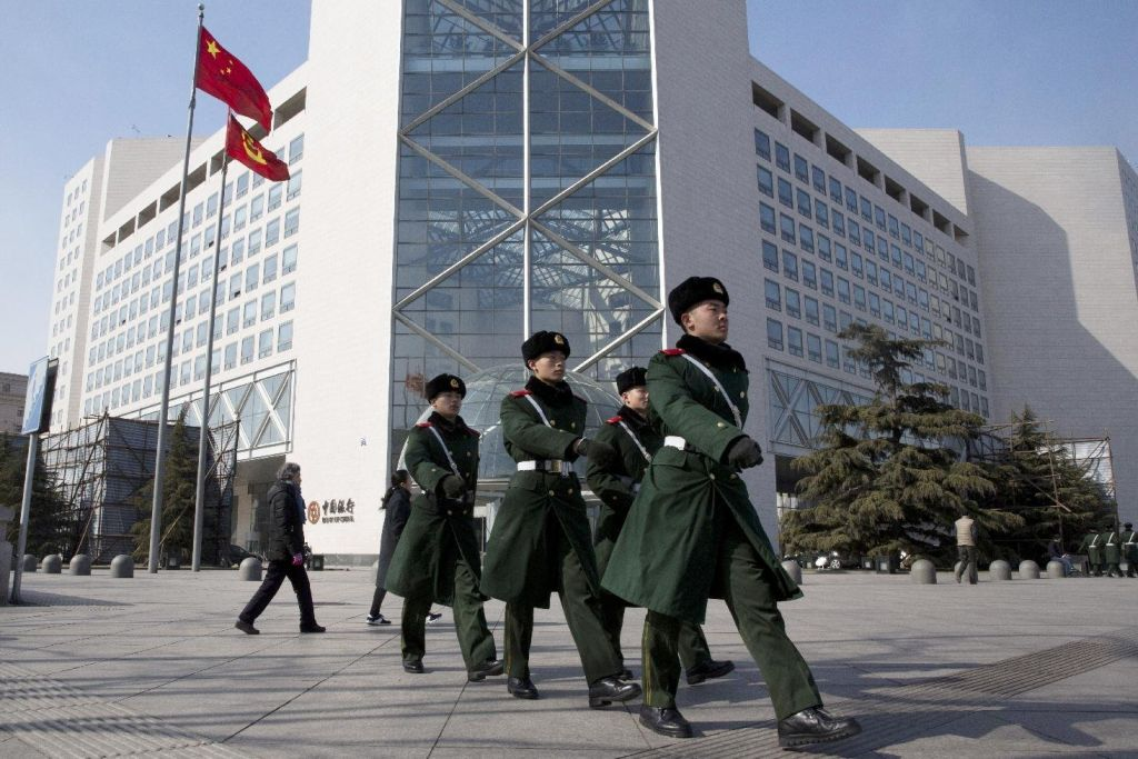 In this Thursday, Feb. 25, 2016, photo, Chinese paramilitary policemen march outside the Bank of China headquarters in Beijing, China. Convicted con man Gilbert Chikli is credited with masterminding a fraud that has cost major multinational companies $1.8 billion in just over two years. Chikli said he laundered 90 percent of his money through China and Hong Kong. Police traced tens of thousands in transfers from Chikli front companies to Bank of China accounts. (AP Photo/Ng Han Guan)