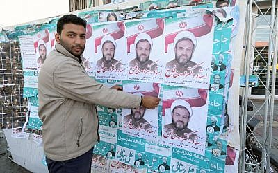 An Iranian man puts up election posters in the city of Qom, some 130 kilometers south of the capital, February 24, 2016. (AFP/Atta Kenare)